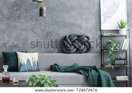 Dark green blanket thrown on the couch with decorative cushions