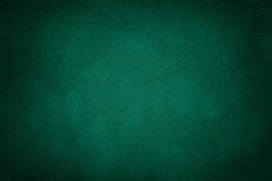 Dark green matte background of suede fabric, closeup. Velvet texture of seamless deep emerald leather. Felt material macro with vignette.