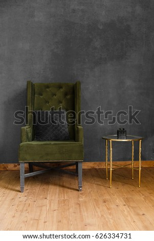 Dark green soft armchair near plaster wall. Arm-chair with fabric upholstery and big vintage mirror in loft style interior #626334731