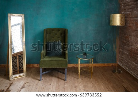 Dark green soft armchair near plaster wall. Arm-chair with fabric upholstery and big vintage mirror in loft style interior #639733552