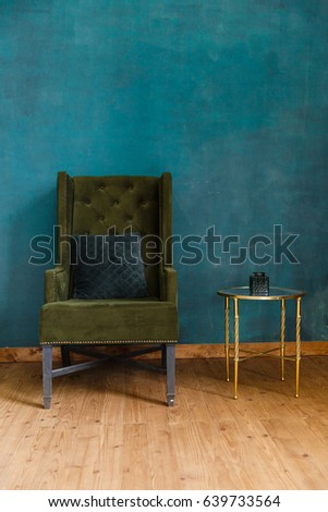Dark green soft armchair near plaster wall. Arm-chair with fabric upholstery and big vintage mirror in loft style interior #639733564