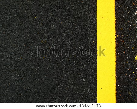 Dark grey asphalt background with yellow line paint