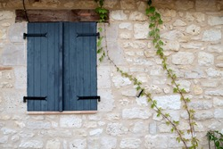 Dark grey window shutters closed in a stone wall surround