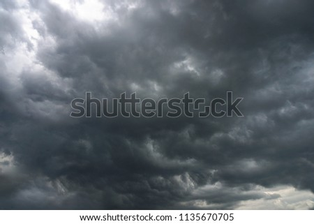 Dark, grim, stormy, rainy sky with rays of light. Scary hurricane clouds. Natural element. Stock Photo for your design #1135670705
