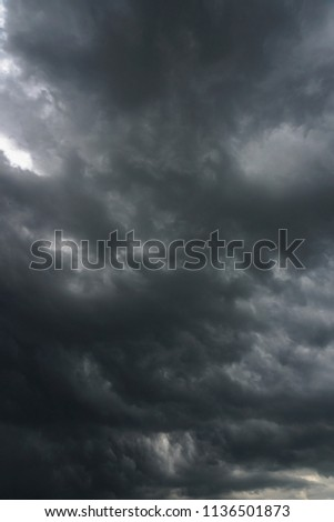 Dark, grim, stormy, rainy sky with rays of light. Scary hurricane clouds. Natural element. Stock Photo for your design #1136501873