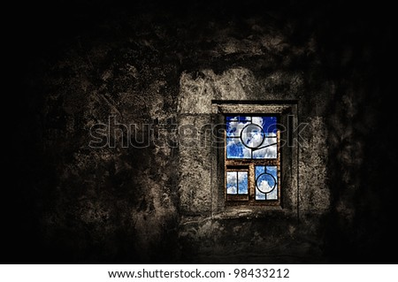 Dark grunge room with old dirty window with leaded glass showing blue sky - hope concept