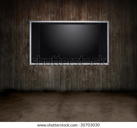 Dark grungy room with a wooden wall and a flat panel TV - stock photo
