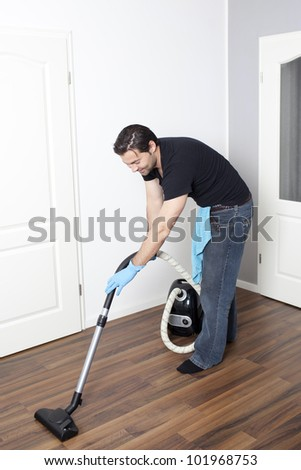 Dark-haired cleaner vacuums the flat