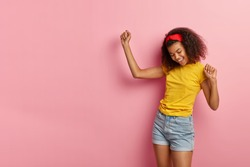 Dark haired energized satisfied African American woman dances actively, enjoys vibes, wears casual yellow t shirt and denim shorts, smiles happily, isolated on pink background, being on party