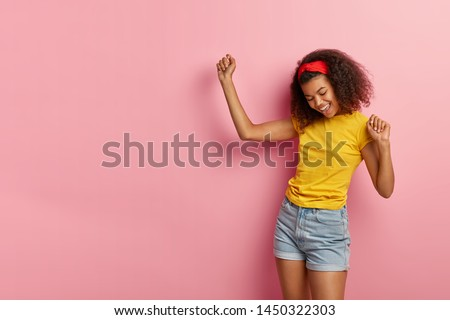 Dark haired energized satisfied African American woman dances actively, enjoys vibes, wears casual yellow t shirt and denim shorts, smiles happily, isolated on pink background, being on party Foto stock ©