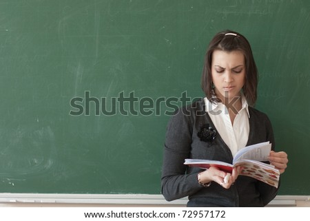 Dark-haired female student reads a notes of the board.