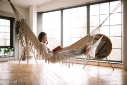 Dark-haired girl dressed in pants, sweater and warm slippers reads a book lying in a hammock in a cozy room with wooden floor and panoramic windows and a round mirror on the floor