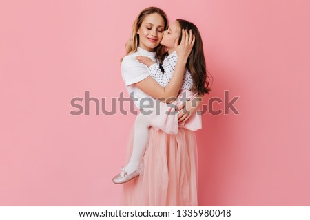 Dark-haired girl gently kisses her mother. Lady holds her daughter in her arms on pink background