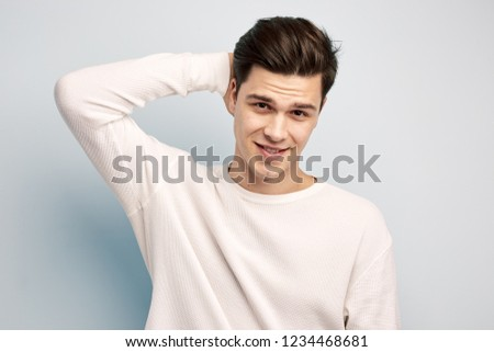 Dark-haired guy dressed in a white long sleeve t-shirt keeps his hand on his head on a white background