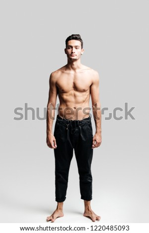 Dark-haired handsome young dancer with  bare torso wearing a black sports pants is standing on a white background
