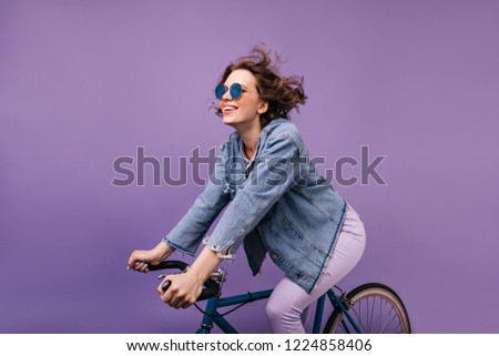 Dark-haired joyful lady chilling during photoshoot on bike. Winsome caucasian girl with wavy hair sitting on bicycle.