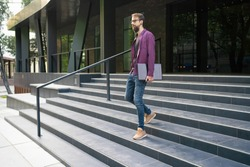 Dark-haired man going down stairs and holding laptop in one hand. Guy in eyeglasses and casual clothes. Building on background. Working outside and freelance concept