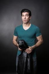 Dark-haired man in green t-shirt visually snorts while holding a leather jacket over his shoulder, isolated on dark background