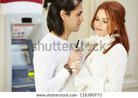 Dark-haired man with credit card in hand and red-haired woman stand face to face, she holds his hand and looks at card
