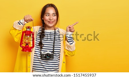 Dark haired mixed race woman camper points fore finger aside, holds gas lamp, dressed casually, uses retro camera, has unforgettable trip in mountains, shows direction against yellow studio background