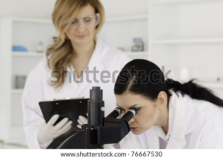 Dark-haired scientist and her assistant conducting an experiment in a lab - stock photo