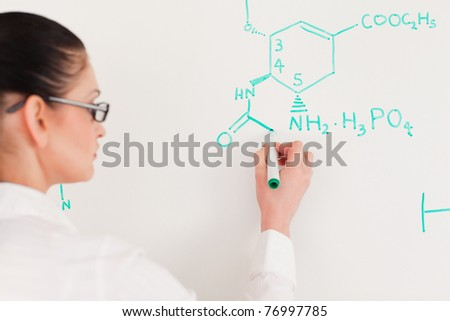 Dark-haired scientist woman writing a formula on a white board in a lab