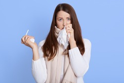 Dark haired unhealthy Caucasian woman with napkin sneezing and holding throat spray in hands to help herself. Rhinitis, cold, sickness and allergy, female uses handkerchief, wearing casual attire.