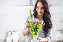 Dark haired woman happily putting fresh colorful tulips into white vase.