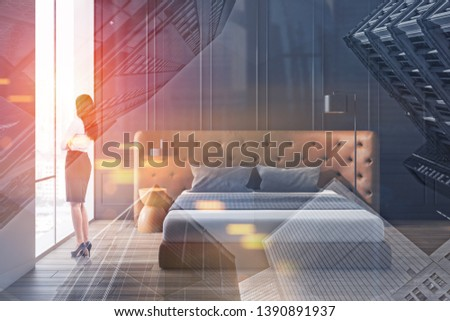 Dark haired woman in formal clothes looking in bedroom window. Minimalistic room interior with king size bed and gray walls. Toned image double exposure #1390891937