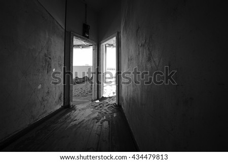 Dark hallway of a deserted building in a ghost town with desert sanding filling the rooms. #434479813