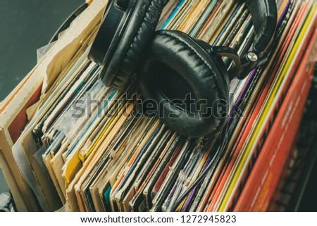 dark headphones lay on stack of retro vinyl records #1272945823