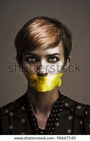 Dark Headshot Of A Distressed And Oppressed Woman Bound And Gagged In Silence With Yellow Masking Tape Covering Her Mouth In A Speak No Evil Conceptual