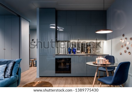Dark home interior in blue with open kitchen and dining area with round table #1389775430