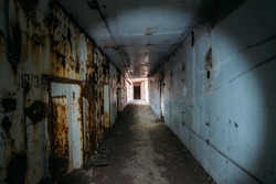 Dark horror creepy corridor or tunnel with light in end in abandoned rusted nuclear power plant in Crimea, toned