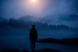 Dark human silhouette in a thick fog against the background of forest, hills and mountain river. Mysterious female figure on desert shore. Apocalyptic landscape, atmospheric pollution.