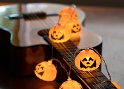 Dark image of halloween pumpkin string lights glowing  on acoustic guitar. Halloween party concept.