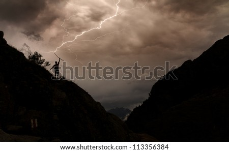 Dark image of lightning striking the staff of a silhouette person in the mountains