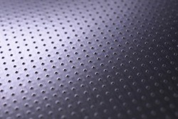Dark industrial metallic background. Tinted violet or purple wallpaper. Perforated aluminum surface with many holes. Perforation rows go into the distance and form a perspective. Macro