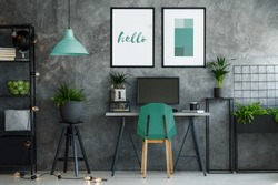 Dark industrial office interior with turquoise decor and modern furniture