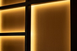 dark interior design element shelf with yellow illumination lighting wall background indoor view concept picture