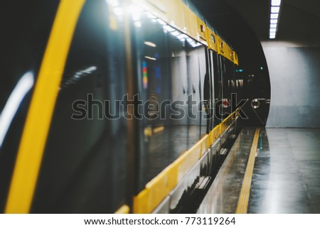 Dark interior of subway station with modern train with closing doors; perspective view of empty underground platform with contemporary black metro train with yellow stripes; Porto, Portugal #773119264