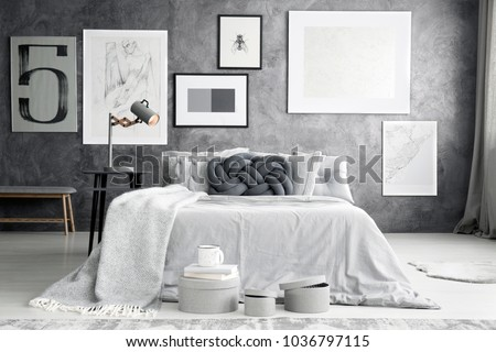 Dark knot pillow on the bed in bright bedroom interior with gallery of posters on concrete wall