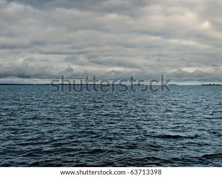 dark lake before storm over rain clouds