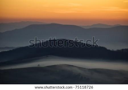 dark landscape with fog between hills and orange sky before sunrise