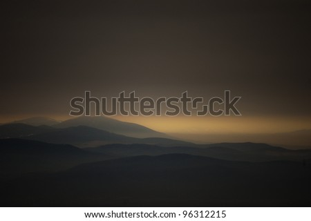 dark landscape with mountains at sunset