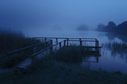Dark landscape with mysterious wooden jetty on lake at night