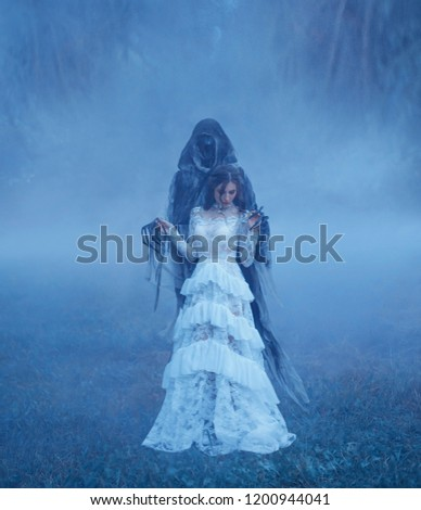 Dark Lord's Bride in white vintage mesh translucent dress and a silver necklace is standing on the frozen grass in a thick blue fog in monster hands. Halloween costume idea. art photo.
