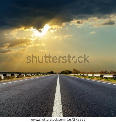 dark low clouds over asphalt road on sunset #167275388