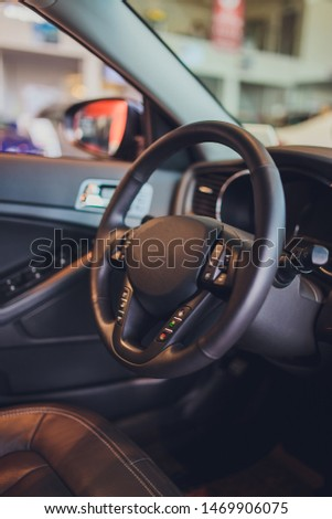 Dark luxury car Interior - steering wheel, shift lever and dashboard. Car interior luxury. Beige comfortable seats, steering wheel, dashboard, climate control, speedometer, display, light wood panels. #1469906075