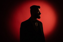 Dark male silhouette. Silhouette of man with beard over red background with copy space